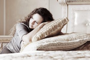 woman-resting-head-on-pillows-after-miscarriage | American Pregnancy Association