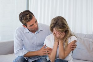 blighted-ovum-couple-sitting-sofa-woman-crying-hands-covering-face | American Pregnancy Association