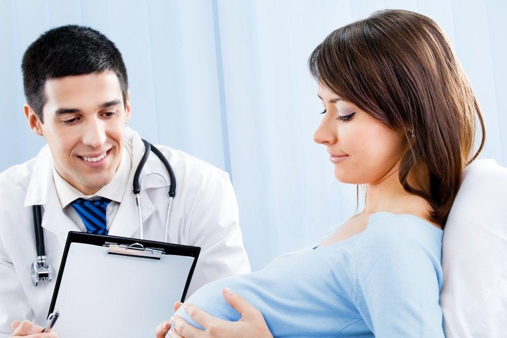 Imagen de una mujer embarazada con un médico las pruebas de los niveles de hCG
