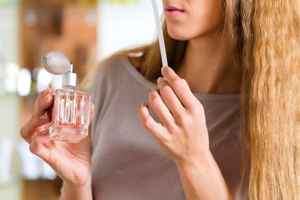 Pregnant woman smelling perfume