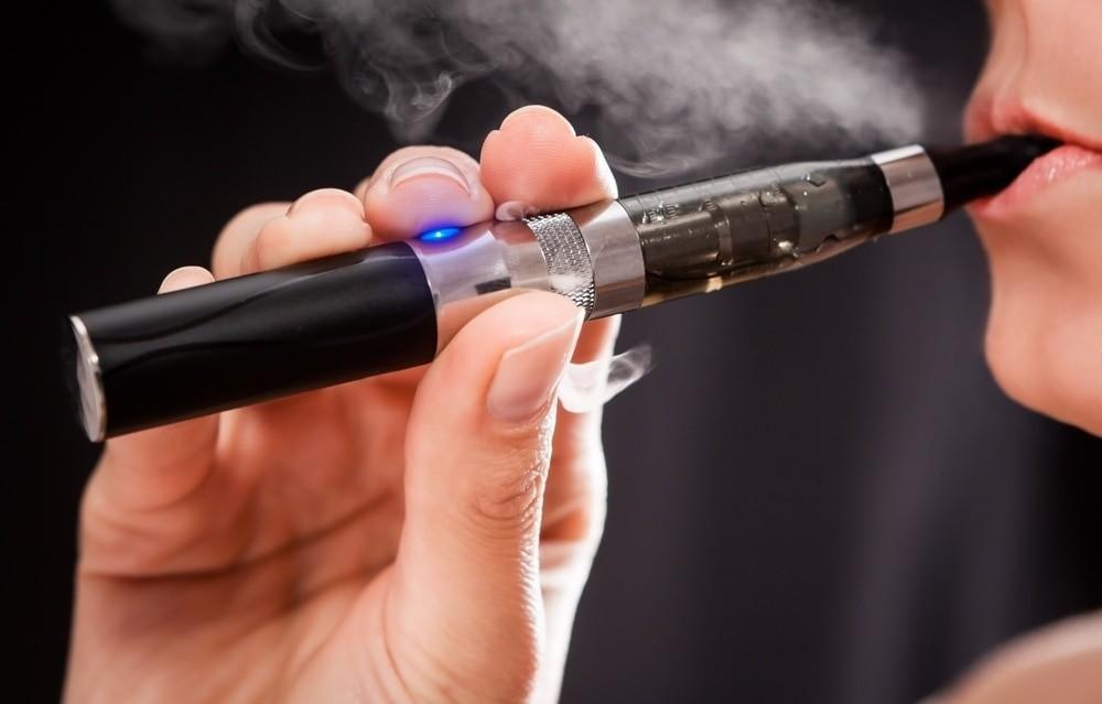Mujer embarazada que usa un cigarrillo eléctrico
