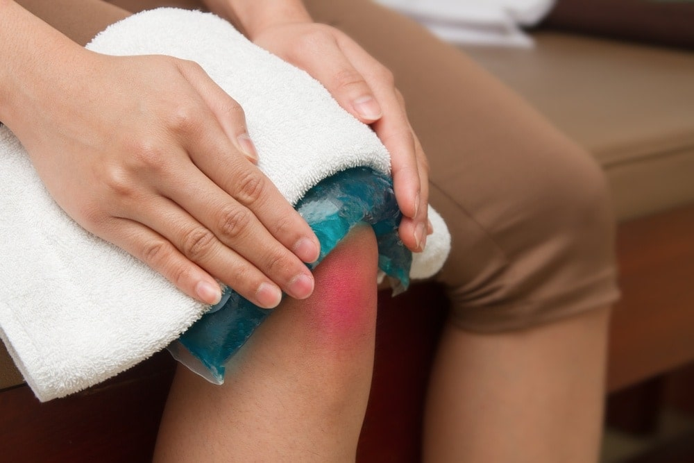 Pregnant woman treating her joint pain with an ice pack