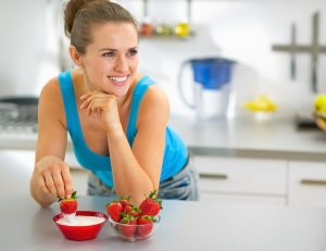 where-to-get-probiotics-naturally-woman-kitchen-strawberries-dip-smiling | American Pregnancy Association