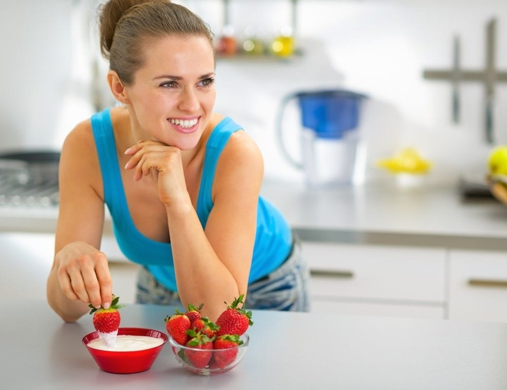 Pregnant woman eating foods high in probiotics.