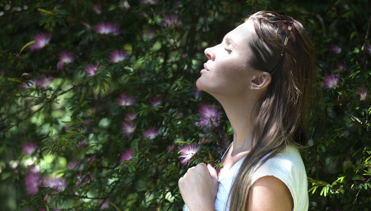 A Woman Takes A Deep Breath In a Garden Unaware Of How Air Pollution Impacts Pregnancy