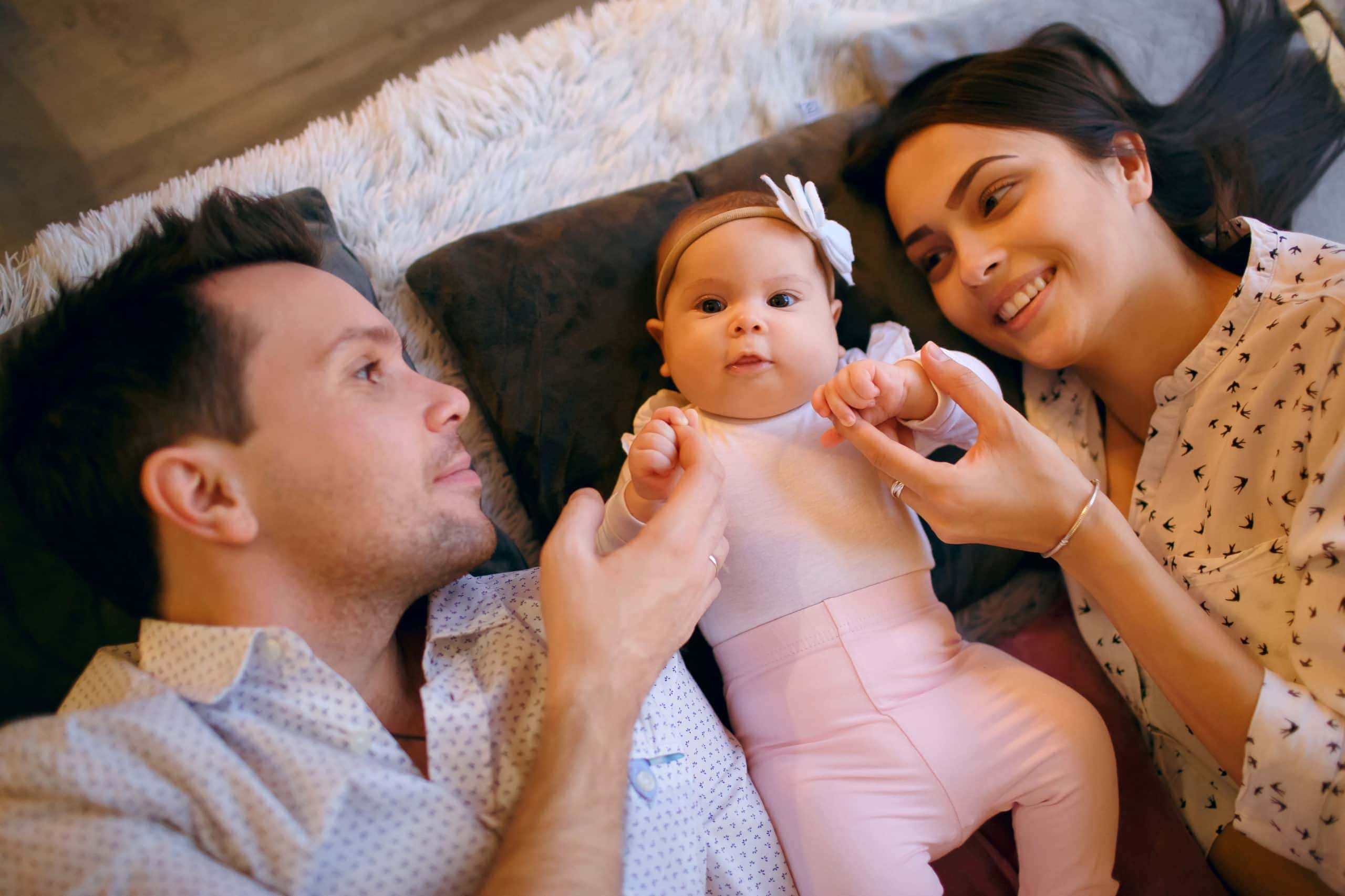 Mother-Father-couple-in-bed-with-new-baby-at home | American Pregnancy Association