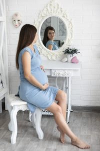 pregnant woman looking in a mirror | American Pregnancy Association